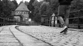 Longueur noire et blanche : l'homme marche vers le bas par le vieux barrage banque de vidéos