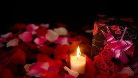 Longueur Valentine de décoration avec des boîte-cadeau, bougie brûlant, et pétales de rose banque de vidéos