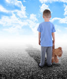 Lonley Boy Standing Alone with Teddy Bear. A young boy is holding a teddy bear and standing on an empty road with clouds in the sky. His shadow is in the horizon Stock Photo