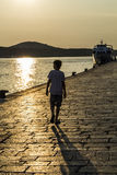 Lonley boy walking by the sea at sunset Stock Photography