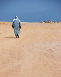 Lonley man going to his camels Royalty Free Stock Photos
