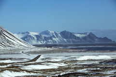 Lonley road in wintertime. Ring road in Iceland in wintertime with volcano mountain landscape in background Royalty Free Stock Image