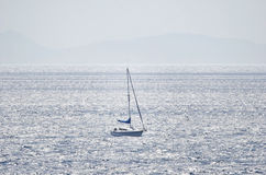 Lonley small sailboat at open sea Stock Image