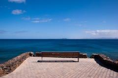 Lonely empty bench in playa blanca. Overlooking fuerteventura Stock Image