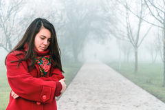 Lonly sad woman portrait in foggy city park. Lonly sad woman in red portrait in foggy city park royalty free stock photography
