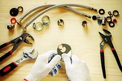 Loodgieter aan het werk met hulpmiddelenloodgieterswerk Stock Afbeelding