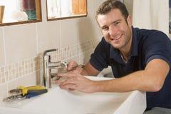 Loodgieter die bij gootsteen het glimlachen werkt Royalty-vrije Stock Foto's