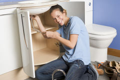 Loodgieter die bij gootsteen het glimlachen werkt Stock Afbeelding