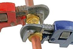 Loodgieter die buisleidingen met moersleutels verscherpen Stock Fotografie