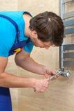 Loodgieter die de radiator bevestigt Stock Foto's