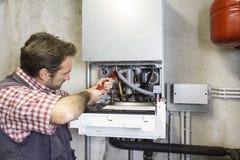 Loodgieter die een condenserende boiler herstellen stock foto's