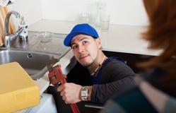 Loodgieter die een keukengootsteen herstellen Stock Fotografie