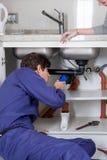Loodgieter die het loodgieterswerk met zijn flitslicht bekijken Royalty-vrije Stock Afbeelding