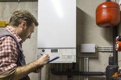 Loodgieter die het onderhoud van een condenserende boiler uitvoert stock foto's