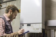 Loodgieter die het onderhoud van een condenserende boiler uitvoert stock fotografie