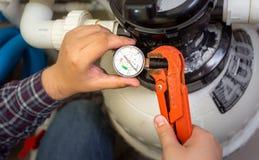 Loodgieter die manometer installeren op pijp royalty-vrije stock afbeelding