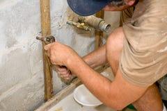 Loodgieter die met Buigtang werkt stock afbeeldingen