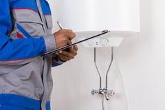 Loodgieter die op klembord schrijven stock afbeeldingen