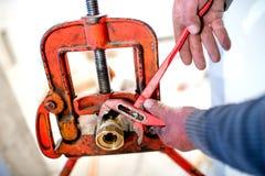 Loodgieter die regelbare moersleutel voor instalation van koperpijpen met behulp van Royalty-vrije Stock Foto's