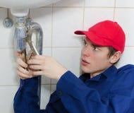 Loodgieter in eenvormige het herstellen oude pijpleiding Stock Foto