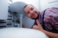 Loodgieter Fixing een Gootsteen in Badkamers stock foto's