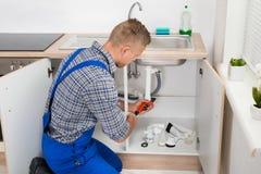 Loodgieter Fixing Sink Pipe stock afbeeldingen