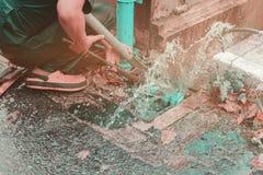 loodgieter het werk de reparatie de gebroken pijp met Regelbare Moersleutels of het Sluiten van Buigtang in gat graaft bij kant v stock foto