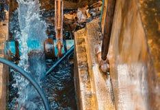 Loodgieter het werk de reparatie de gebroken pijp met Regelbare Moersleutels of het Sluiten van Buigtang in gat graaft bij kant v royalty-vrije stock afbeelding
