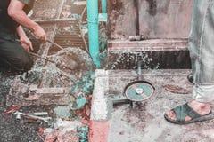 Loodgieter het werk de reparatie de gebroken pijp met Regelbare Moersleutels of het Sluiten van Buigtang in gat graaft bij kant v royalty-vrije stock fotografie