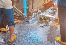 Loodgieter het werk de reparatie de gebroken pijp met Regelbare Moersleutels of het Sluiten van Buigtang in gat graaft bij kant v royalty-vrije stock foto