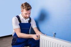 Loodgieter Installing Radiator stock foto's