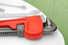 Loodgieter` s hulpmiddelen op het deksel van de toiletzetel stock foto's
