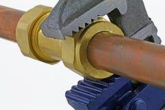 Loodgieter` s regelbare moersleutel die koperbuisleidingen verscherpen Stock Foto's