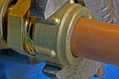 Loodgieter` s regelbare moersleutel die koperbuisleidingen verscherpen Royalty-vrije Stock Fotografie