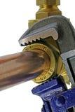 Loodgieter` s regelbare moersleutel die koperbuisleidingen verscherpen Royalty-vrije Stock Foto