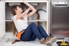 Loodgietervrouw die DE pipe van de keuken herstellen Royalty-vrije Stock Foto's
