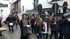 Looe, Cornwall, UK, February 16, 2019. Mixed group of `Extinction Rebellion` protesters, marching through the Cornish town of Looe stock footage