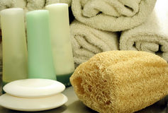 Loofah Sponge and Bath Accessories. This is an image of a loofah sponge with rolled towels, soap, shampoo, conditioner, and moisturizer stock photo