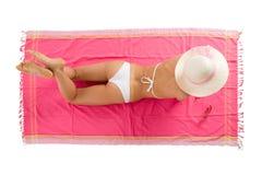 Looien die van het meisje op de strandhanddoek ligt stock foto