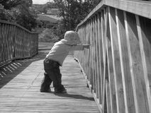 LOOK!. B&W - Young child pointing earnestly through the sides of a bridge Stock Images