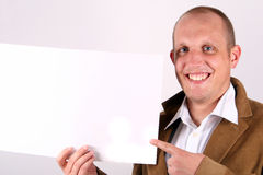 Look At This. A young businessman is amiling and holds a sign and points at it! White sign to write on Stock Photos