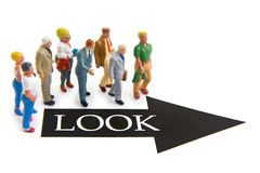 Look. Miniature figures with look text and arrow Stock Photography