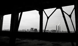 Look from abandoned factory workshop on smoking smokestacks Royalty Free Stock Photos