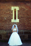 A look from afar on a bride standing under a small window stock images
