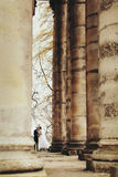 A look from afar on the stunning couple walking among the pillar. S of an old cathedral Stock Images