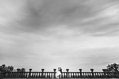 A look from afar on a wedding couple sitting on the balcony unde. R a gray sky Royalty Free Stock Photos