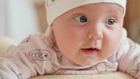 The look of the baby in the camera close up shot. The baby looks around and then smiles and laughs. Concept of caring for children, parental love stock footage