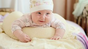 The look of the baby in the camera close up shot. The baby looks around and then smiles and laughs. Concept of caring for children, parental love stock video footage
