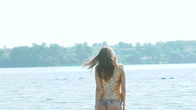 Look back of girl going in water and turning around. Slowly.  stock footage