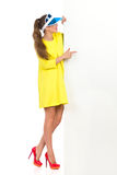 Look At This Banner. Side view of young woman in yellow mini dress, blue plastic sun visor and red high heels pointing at white big banner. Full length studio Royalty Free Stock Images